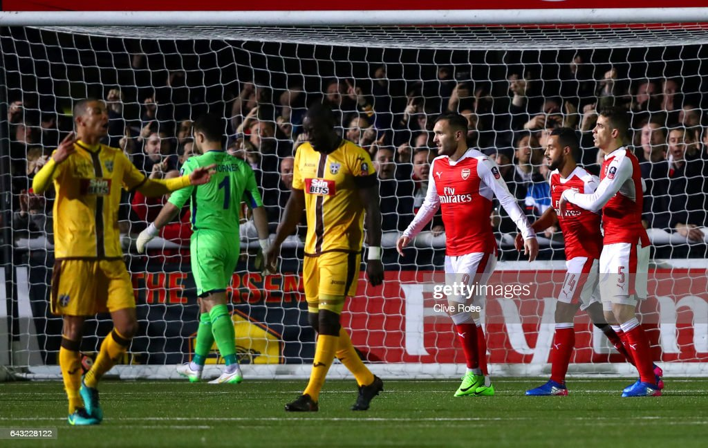 Theo Walcott of Arsenal celebrates with team-mates after scoring his team's second goal and his 100th for the club during the Emirates FA Cup fifth round match between Sutton United and Arsenal on February 20, 2017 in Sutton, Greater London.
