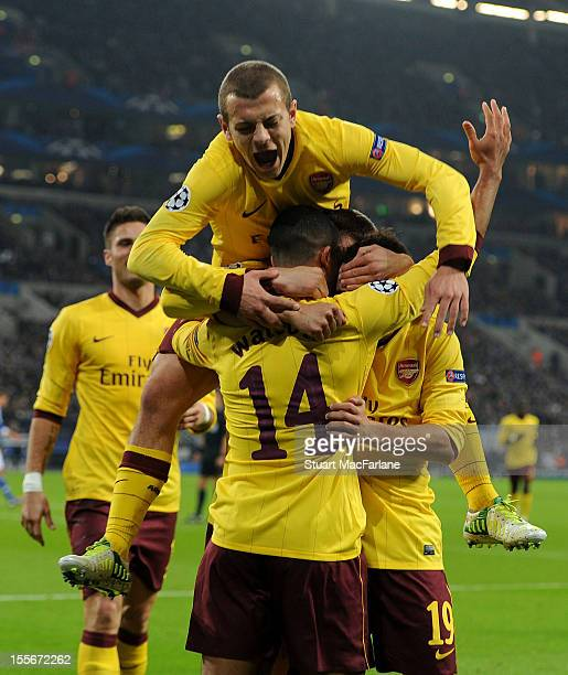 Theo Walcott of Arsenal celebrates with teammates Jack Wilshere and Santi Cazorla after scoring his team's first goal during the UEFA Champions...