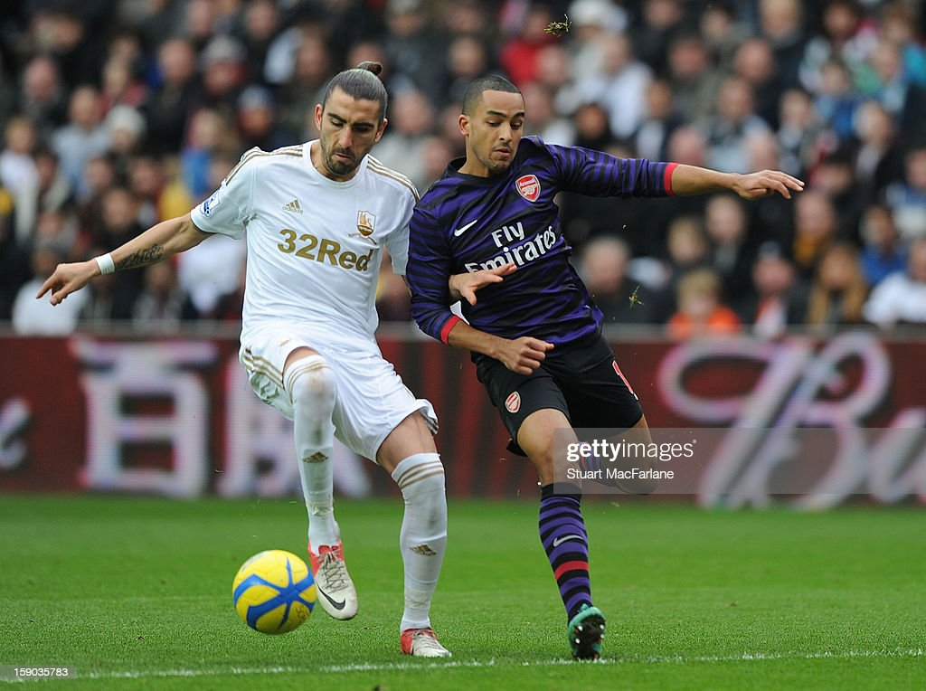 Theo Walcott of Arsenal challenged by Chico Flores of Swansea during the FA Cup Third Round match between Swansea City and Arsenal at the Liberty Stadium on January 6, 2013 in Swansea, Wales.