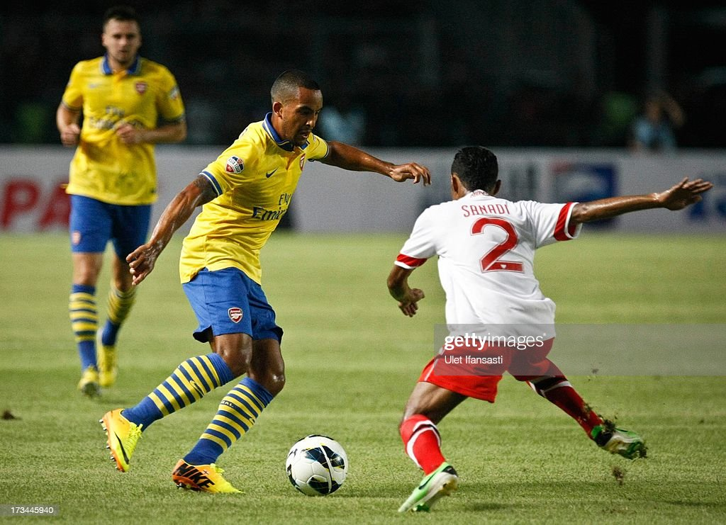 Theo Walcott of Arsenal challenges Ruben Sanadi (R) of Indonesia All-Stars during the match between Arsenal and the Indonesia All-Stars at Gelora Bung Karno Stadium on July 14, 2013 in Jakarta, Indonesia.