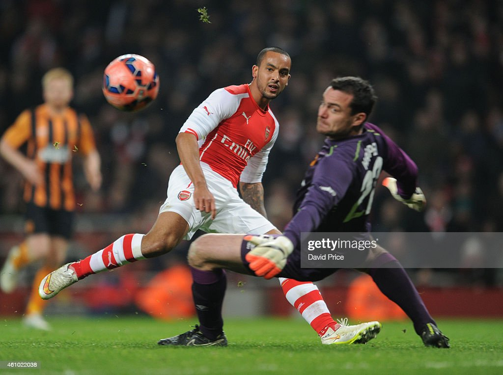 Theo Walcott of Arsenal clips the ball past Steve Harper of Hull during the match between Arsenal and Hull City in the FA Cup 3rd Round at Emirates Stadium on January 4, 2015 in London, England.