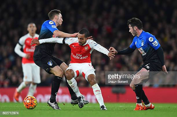 Theo Walcott of Arsenal competes for the ball against Simon Francis and Adam Smith of Bournemouth during the Barclays Premier League match between...