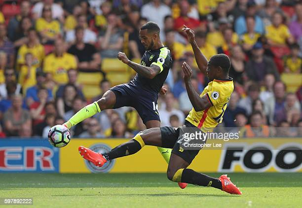 Theo Walcott of Arsenal crosses past Christian Kabasele of Watford during the Premier League match between Watford and Arsenal at Vicarage Road on...