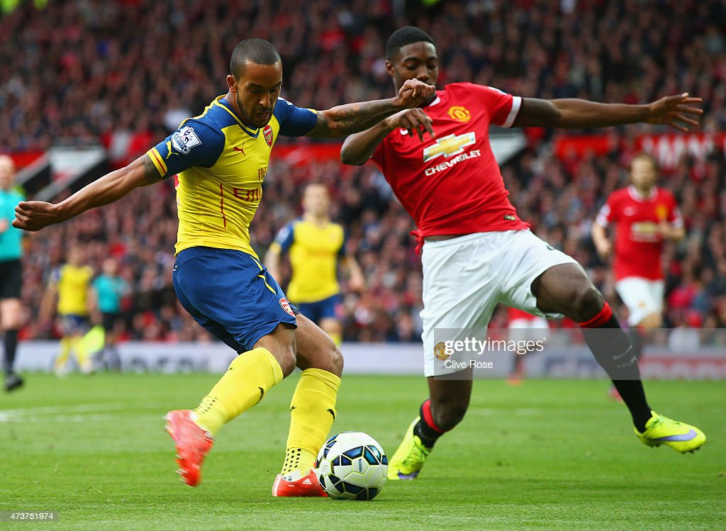 Theo Walcott of Arsenal crosses the ball which deflects of off Tyler Blackett of Manchester United for an own goal during the Barclays Premier League match between Manchester United and Arsenal at Old Trafford on May 17, 2015 in Manchester, England.
