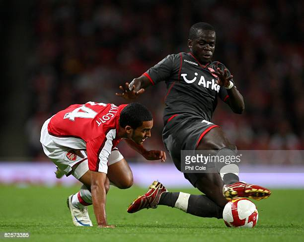 Theo Walcott of Arsenal gets tackled by Cheick Tiote of FC Twente during the UEFA Champions League third qualifying round second leg match between...