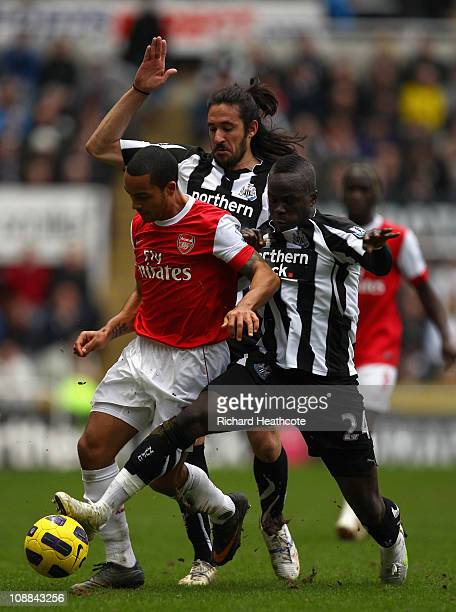 Theo Walcott of Arsenal holds off Jonas Gutierrez and Cheik Tiote of Newcastle during the Barclays Premier League match between Newcastle United and...