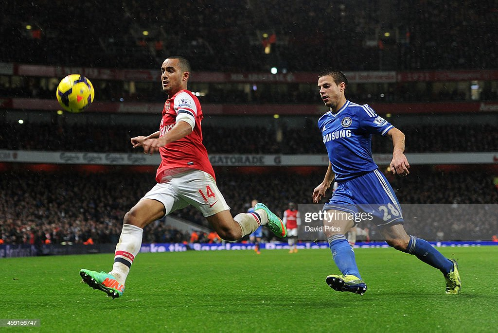Theo Walcott of Arsenal is closed down by Cesar Azpilicueta of Chelsea during the match between Arsenal and Chelsea in the Barclays Premier League at Emirates Stadium on December 23, 2013 in London, England.