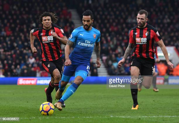 Theo Walcott of Arsenal is takes on Nathan Ake and Steve Cook of Bournemouth during the Premier League match between AFC Bournemouth and Arsenal at...