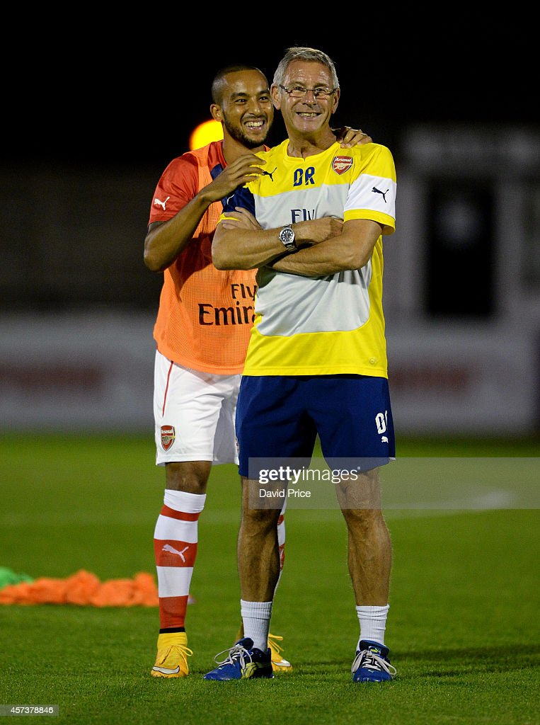 Theo Walcott of Arsenal leans on Arsenal U21 Kitman Denis Rockall during his warm up before the match between Arsenal U21 and Blackburn U21 in the Barclays Premier U21 League at Meadow Park on October 17, 2014 in Borehamwood, England.