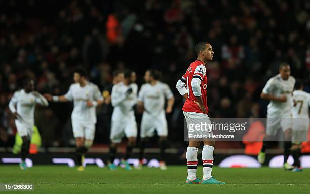 Theo Walcott of Arsenal looks dejected as Swansea celebrate their first goal during the Barclays Premier League match between Arsenal and Swansea...