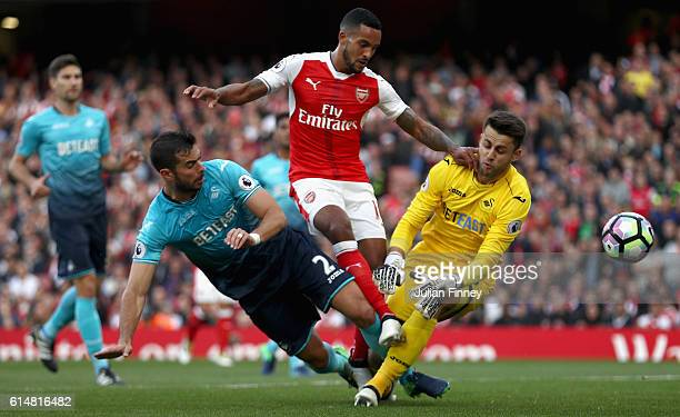 Theo Walcott of Arsenal scores his sides first goal past Lukasz Fabianski of Swansea City during the Premier League match between Arsenal and Swansea...