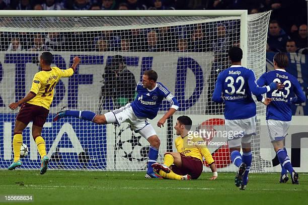 Theo Walcott of Arsenal scores the first goal against Benedikt Hoewedes of Schalke Joel Matip and Christian Fuchs of Schalke during the UEFA...
