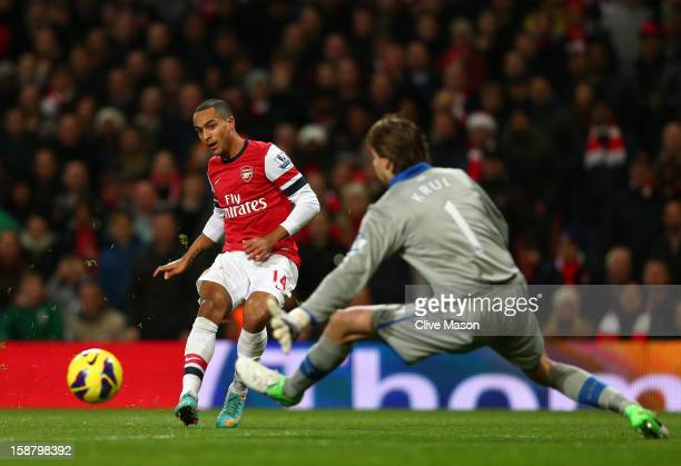 Theo Walcott of Arsenal scores the first goal past Tim Krul of Newcastle United during the Barclays Premier League match between Arsenal and...