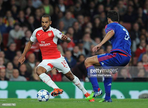 Theo Walcott of Arsenal takes on Alberto Botia of Olympiacos during the UEFA Champions League match between Arsenal and Olympiacos at Emirates...