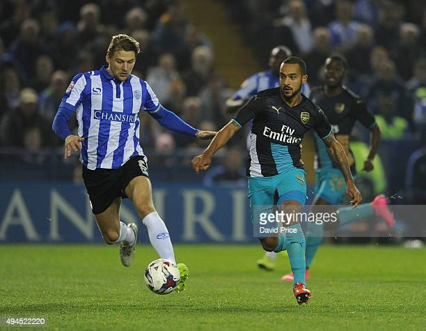 Theo Walcott of Arsenal takes on Glenn Loovens of Sheffield Wednesday during the Capital One Cup 4th Round match between Sheffield Wednesday and...