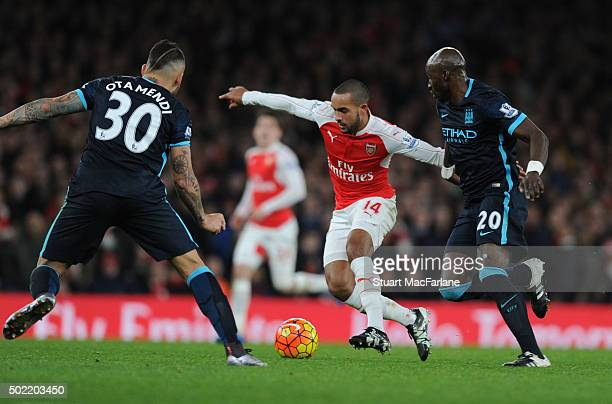 Theo Walcott of Arsenal takes on Nicolas Otamendi and Eliaquim Mangala of Man City during the Barclays Premier League match between Arsenal and...