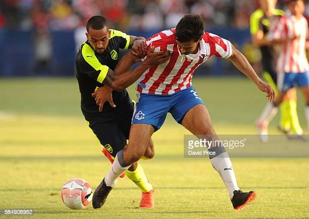 Theo Walcott of Arsenal takes on Oswaldo Alanis of CD Guadalajara during the match between Arsenal and CD Guadalajara at StubHub Center on July 31...