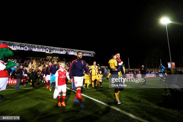 Theo Walcott of Arsenal walks out in front of his teammates and the Sutton United players during the Emirates FA Cup fifth round match between Sutton...