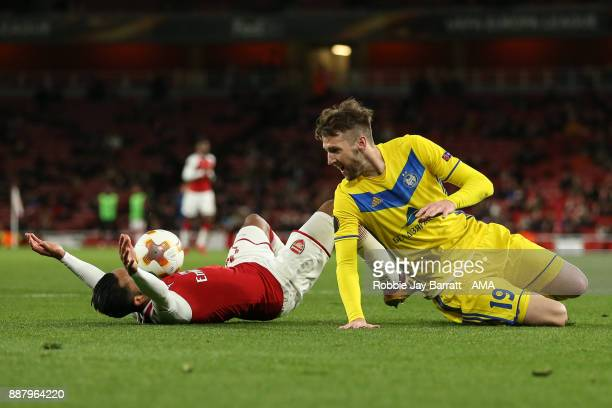 Theo Walcott of Arsenal wins a penalty after a tackle from Nemanja Milunovic of Bate Borisov during the UEFA Europa League group H match between...