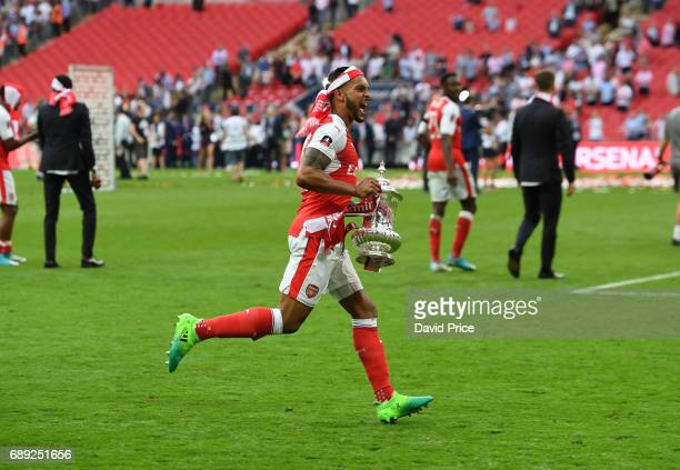 Theo Walcott of Arsenal with the FA Cup Trophy after the match between Arsenal and Chelsea at Wembley Stadium on May 27 2017 in London England