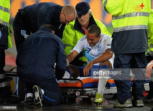 Theo Walcott of England is stretchered off injured during the UEFA EURO 2012 Group G Qualifier between Switzerland and England at St Jakob Park on...