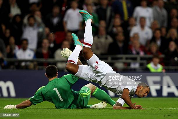 Theo Walcott of England is upeneded by goalkeeper Aldo Junior Simoncini of San Marino during the FIFA 2014 World Cup Group H qualifying match between...