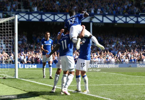 Theo Walcott of Everton celebrates with teammates after scoring his team's fourth goal during the Premier League match between Everton FC and...