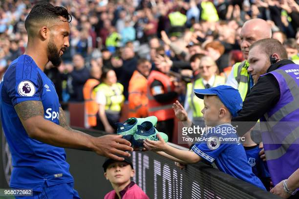 Theo Walcott of Everton hands his boots to a young Everton fan after the Premier League match between West Ham United and Everton at London Stadium...