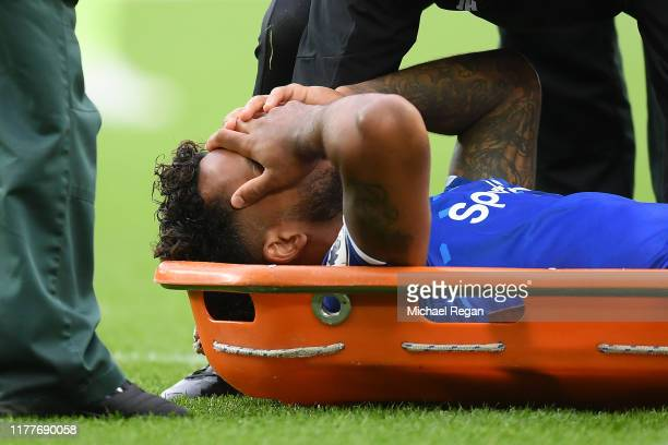 Theo Walcott of Everton receives medical treatment after he is hit on the head from a ball after a cross by Raheem Sterling of Manchester City during...