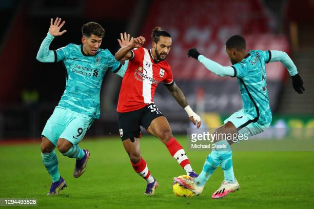 Theo Walcott of Southampton is challenged by Roberto Firmino and Georginio Wijnaldum of Liverpool during the Premier League match between Southampton...