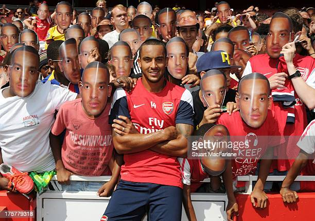 Theo Walcott poses with Arsenal fans in Theo Walcott masks after the Arsenal Training session and Members Day at the Emirates Stadium on August 08,...