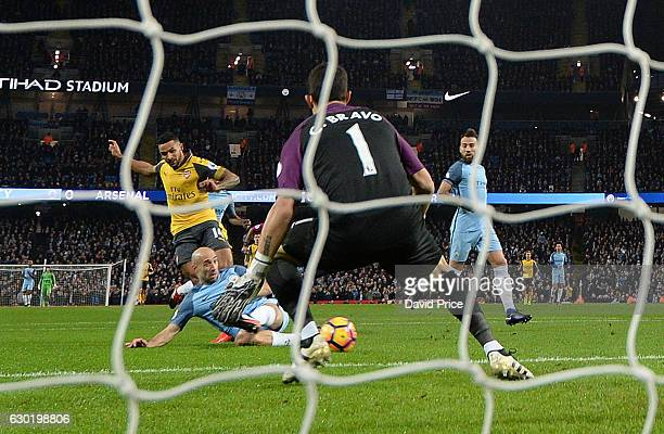 Theo Walcott scores a goal for Arsenal past Claudio Bravo of Man City during the Premier League match between Manchester City and Arsenal at Etihad...