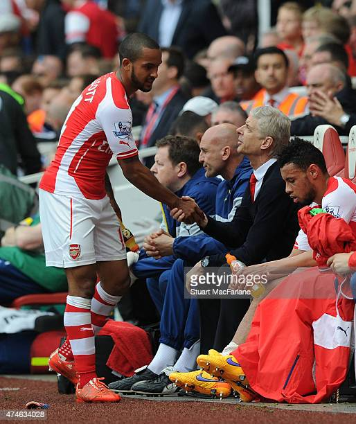 Theo Walcott shakes hands with Arsenal manager Arsene Wenger after being substituted during the Barclays Premier League match between Arsenal and...