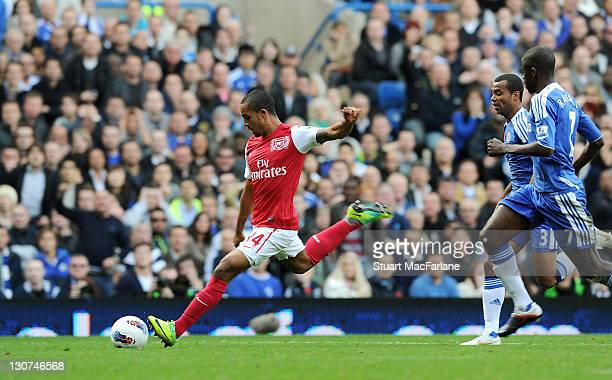 Theo Walcott shoots past Chelsea goalkeeper Petr Cech to score the third goal during the Barclays Premier League match between Chelsea and Arsenal at...