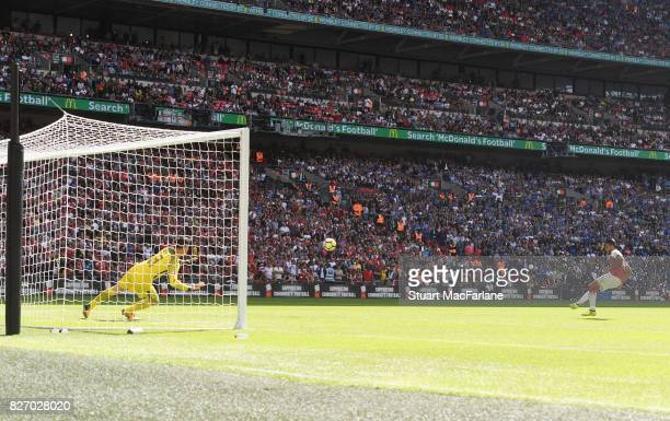 Theo Walcott shoots past Chelsea goalkeeper Thibaut Courtois to score in the penaly shoot out during the FA Community Shield match between Chelsea...