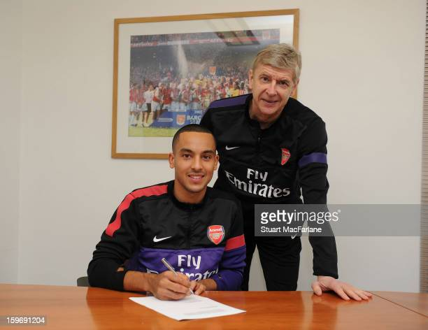 Theo Walcott signs his new Arsenal contract with manager Arsene Wenger at the Arsenal Training Ground, London Colney on January 18, 2013 in St...