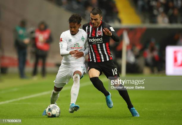 Theodor Gebre Selassie of SV Werder Bremen is challenged by Filip Kostic of Eintracht Frankfurt during the Bundesliga match between Eintracht...