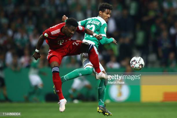 Theodor Gebre Selassie of Werder Bremen and David Alaba of Bayern Munich battle for possession during the DFB Cup semi final match between Werder...