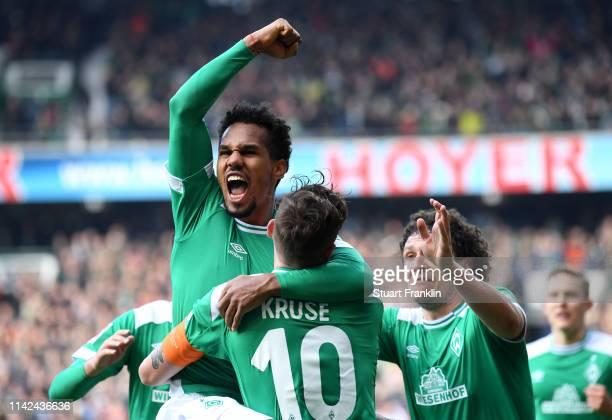 Theodor Gebre Selassie of Werder Bremen celebrates with teammate Max Kruse after scoring his team's second goal during the Bundesliga match between...