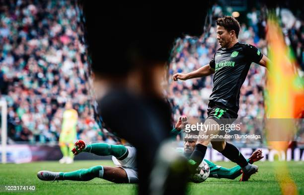 Theodor Gebre Selassie of Werder Bremen in action against Takuma Asano of Hannover 96 during the Bundesliga match between SV Werder Bremen and...
