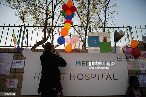 Theodora Alexandrakis ties balloons with handwritten getwell wishes to the fence outside the Mediclinic Heart Hospital where former South African...