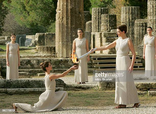 Theodora Siarkou the actress acting as a high priestess holds the torch with the Olympic flame lit using the rays of the sun in the ancient sanctuary...
