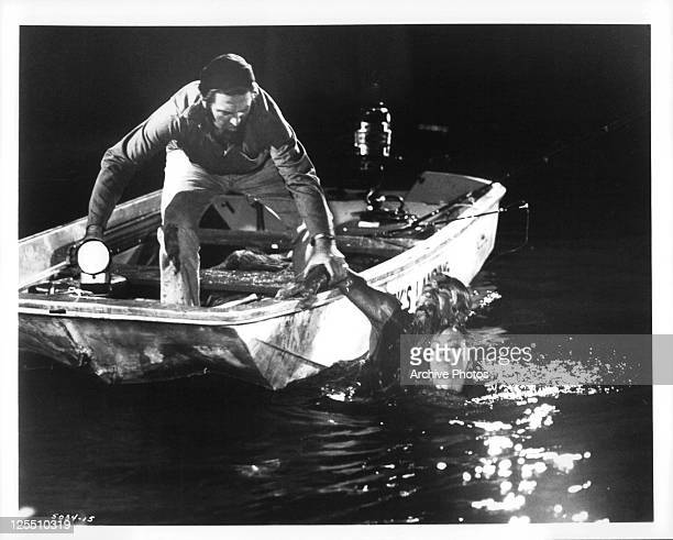 Theodore Bikel on a boat helping Rod Taylor and Suzy Kendall from the water in a scene from the film 'Darker Than Amber' 1970