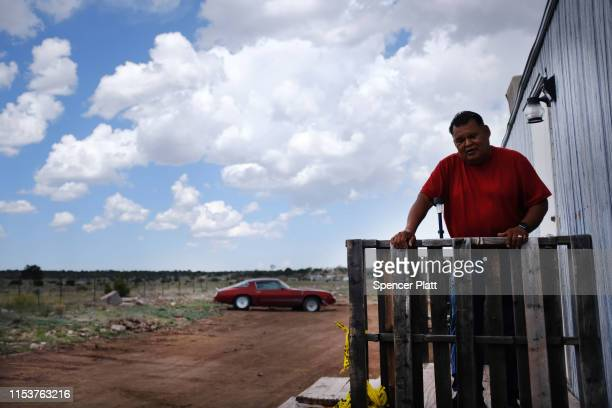 Theodore Bryan a member of the Navajo Nation watches as workers prepare to install a water tank in his yard on June 04 2019 in Thoreau New Mexico Due...