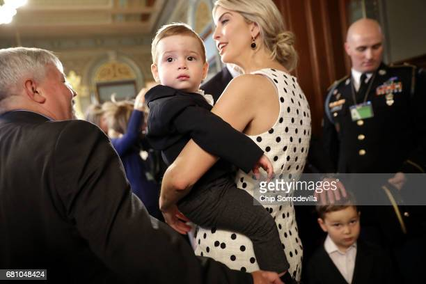 Theodore James Kushner is held by his mother Ivanka Trump as they greet members of the armed forces and their families during an event celebrating...