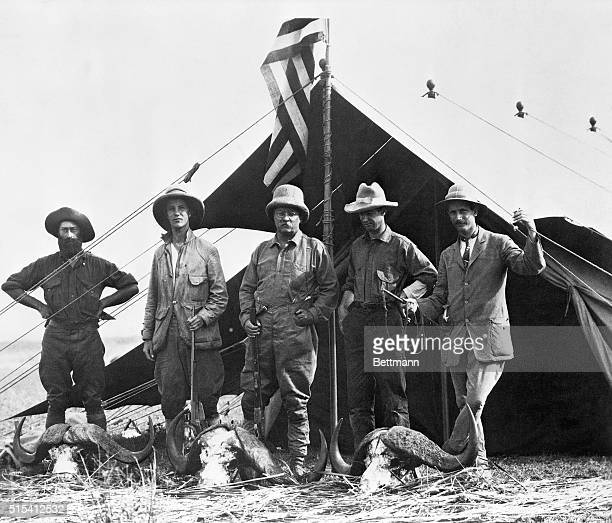 Theodore Roosevelt and his expeditionary companions pose with three water buffalo heads. Photo taken in British East Africa shows R.J. Cuninghame,...