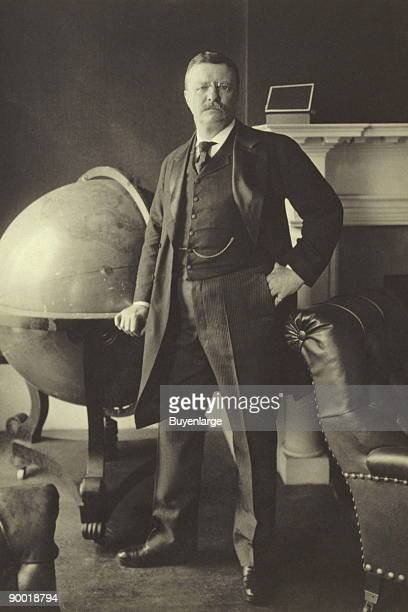 Theodore Roosevelt fulllength portrait standing beside large globe facing front