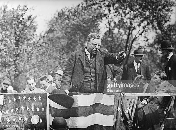 Theodore Roosevelt standing on a podium pointing into the crowd during a campaign rally speech Ca 1900s