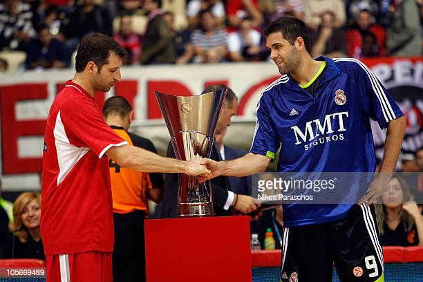 Theodorus Papaloukas, #4 of Olympiacos Piraeus and Felipe Reyes, #9 of Real Madrid giving handshake in front of the season's Trophy during the...