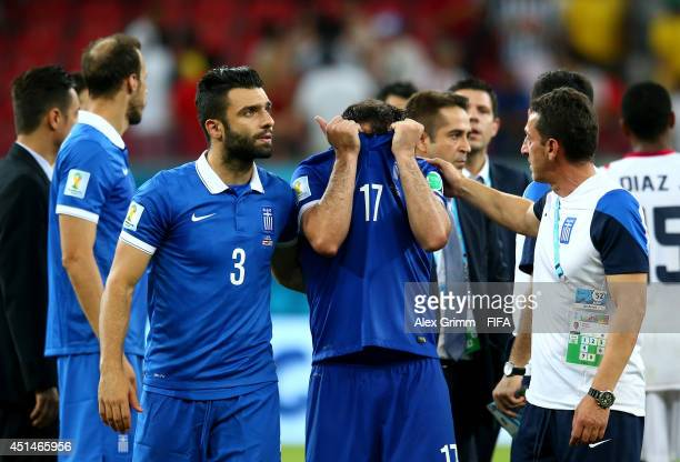 Theofanis Gekas and Giorgos Tzavellas react after the defeat in the 2014 FIFA World Cup Brazil Round of 16 match between Costa Rica and Greece at...